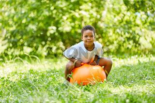 Afrikanischer Junge sitzt auf einem Hüpfball