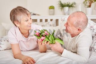 Senior schenkt seiner Frau Blumen