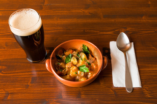 Traditional Irish Stew with a pint of stout beer and a spoon