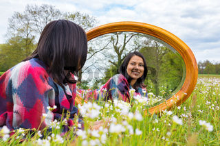 Woman lying with mirror in flowering meadow