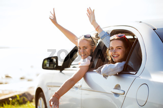 happy teenage girls or women in car at seaside