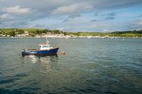 Blue fishing motor boat moored in estuary at Appledore, Devon