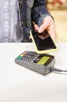 Kunde mit Smartphone am Kartenterminal