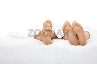 Heels of two people stick out from under a white bed-sheet