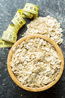 Oat flakes in bowl and measuring tape.
