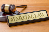 A gavel and a name plate with the engraving Martial law