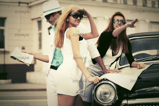 Young fashion people with a road map next to vintage car