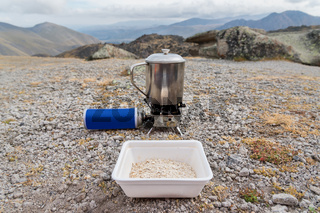 A plastic cup with oatmeal waiting for a while in a metal mug on a portable torch with a gas cylinder will boil water