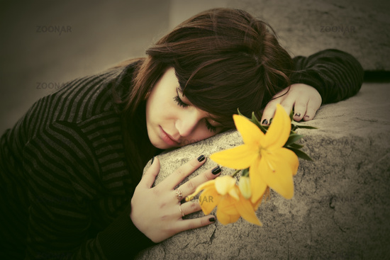 Sad young woman with a flowers lying on tombstone