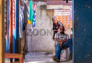 Cuban people in colorful house with clothes