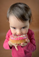 Little girl eating donuts