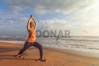 Woman doing yoga asana Virabhadrasana 1 Warrior Pose on beach on