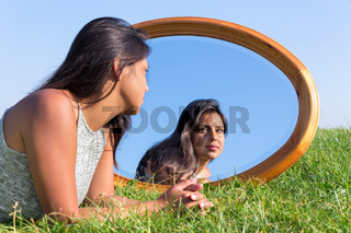 Woman lying on grass outside looking in mirror