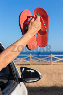 Arm in car showing bath slippers at sea