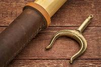 wooden oar and brass oarlock on rustic wood