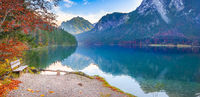 Wooden bench on Alpsee lake shore