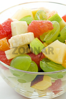 Fresh fruit salad mix as closeup in a bowl on white background