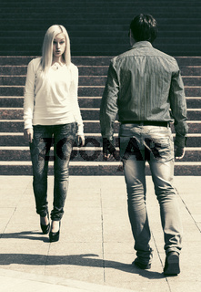 Young fashion man and woman flirting walking in a city street