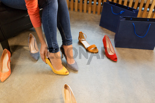 young woman trying high-heeled shoes at store