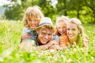 Eltern und Kinder liegen glücklich im Gras