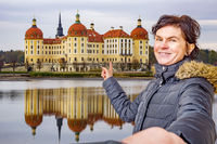 Woman points to the castle of Moritzburg