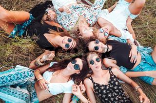 Six girls lie on the grass