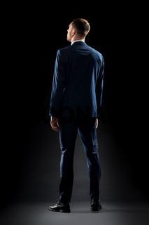 businessman in suit over black