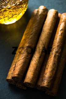 Cigars with alcohol on dark background