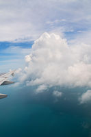 View from an airplane on wing of an airplane and cumulus clouds over the sea