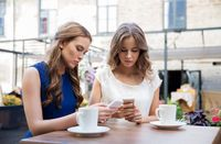 young women with smartphones and coffee at cafe