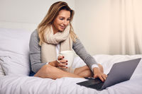 Attractive woman sitting on her bed with coffee