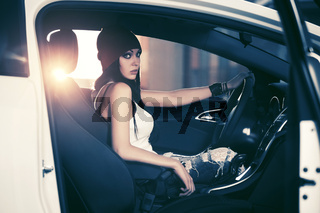 Young fashion woman in tank top and a beanie sitting in a car