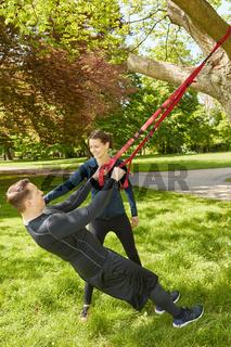 Mann macht Schlingentraining an Baum