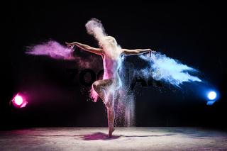 Girl in color dust cloud posing in studio
