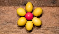 Pattern of painted eggs on wooden table for Easter