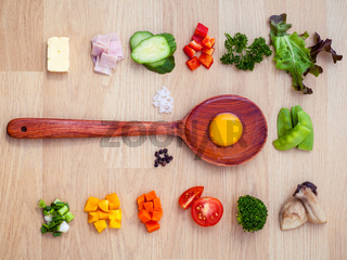 Ingredients of homemade omelet on wooden panel.Various vegetable and seasoning for cooking breakfast. Food background concept flat lay on wooden table.