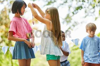 Mädchen überreicht der Siegerin eine Medaille