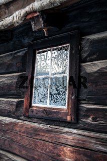 Rustic house with snowflakes on window