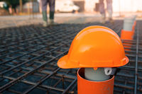 Orange safety helmet at construction site with blurry background