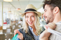Glücklicher blonder Teenager beim Shopping