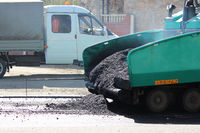 Car for asphalt road with crumb of asphalt in a scoop.