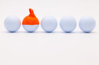 White golf balls with funny cap on the white background.