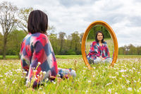 Woman sitting with mirror in blooming meadow