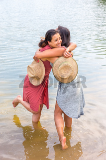 Two women embracing each other in water