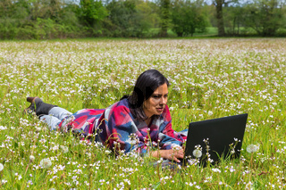Woman lying in field of flowers with  computer