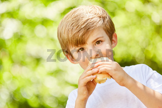 Hungriger Junge isst Baguette als Pausenbrot