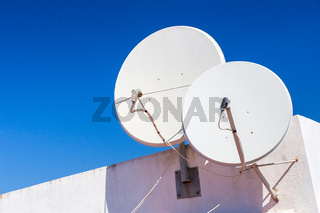 Two white satellite dishes on house wall