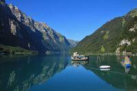 Clear blue summer day at lake Klontalersee. Glarnisch, mountain range reflecting  in the water. Landscape in Switzerland.