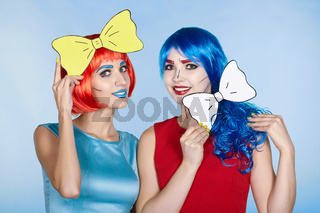 Females in red and blue wigs on blue background. Girls with yellow bow-tie in hands