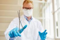 Chirurg bei Operation mit Klemme